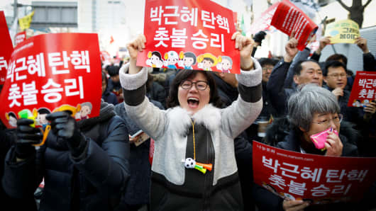 People celebrate after hearing that President Park Geun-hye's impeachment was accepted in front of the Constitutional Court in Seoul, South Korea, March 10, 2017.
