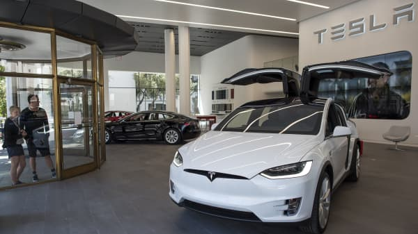 Pedestrians look at Tesla Motors Inc. vehicles displayed at the company's new showroom in San Francisco, California.