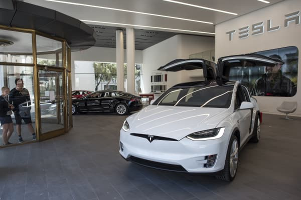 Pedestrians look at Tesla Motors Inc. vehicles displayed at the company's new showroom in San Francisco, California.