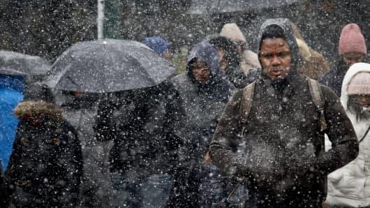 Pedestrians walk through wet snow.