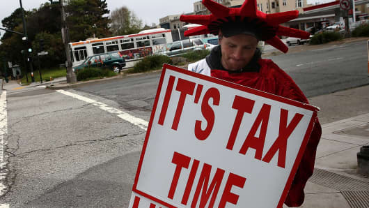 A man holds a sign advertising income tax services in San Francisco, California.