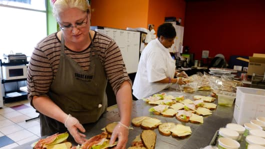 Donna Dickens, left, and Kathrine Lewis, prepare sandwiches together inside the Share Good Foods kitchen in Englewood, Colorado.