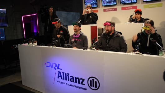 Professional drone racers with the Drone Racing League laugh during a race.