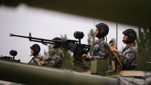 Soldiers of People's Liberation Army (PLA) stand inside tanks at a drill during an organized media tour at a PLA engineering academy.