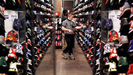 An employee arranges a sneaker display at a Foot Locker Inc. store inside the South Park Mall in Strongsville, Ohio.