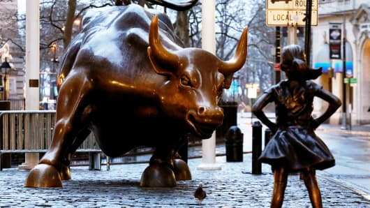 A statue of a girl facing the Wall Street Bull in the financial district in New York.