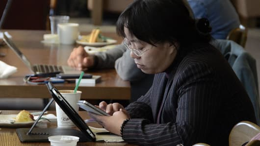 People access the internet on their smartphones and laptops in a cafe in Beijing, China.