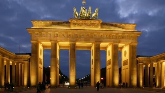 People walk past the illuminated Brandenburg Gate