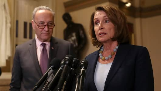 Senate Minority Leader Charles Schumer (L) (D-NY) looks on as House Minority Leader Nancy Pelosi (D-CA) speaks to reporters during a news conference at the U.S. Capitol.