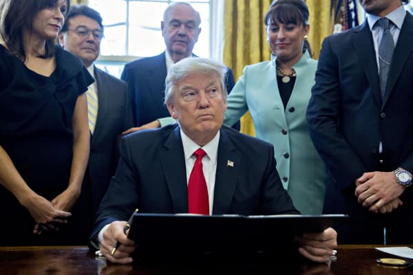 U.S. President Donald Trump pauses after signing an executive order in the Oval Office of the White House surrounded by small business leaders January 30, 2017 in Washington, DC.