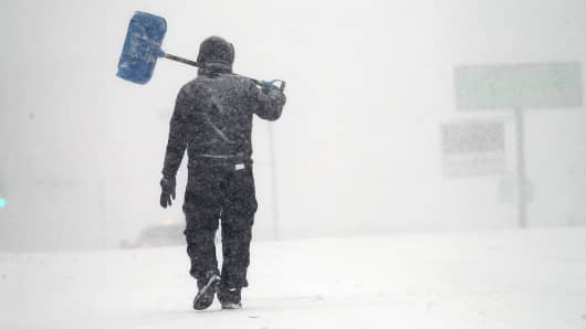 A pedestrian carries a shovel through white-out conditions during a winter storm in downtown Worcester, MA on Mar. 14, 2017.
