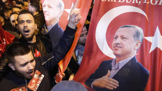 Demonstrators with banners of Turkish President Recep Tayyip Erdogan gather outside the Turkish consulate to welcome the Turkish Family Minister, Fatma Betul Sayan Kaya