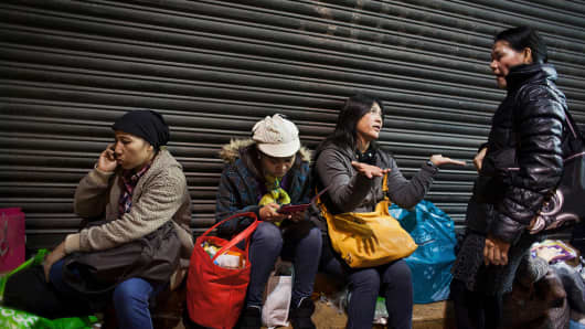 A group of Filipino women sit and chat and eat in the streets in Hong Kong Central on a Sunday evening.