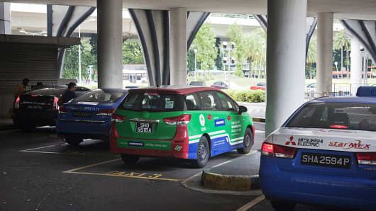 A taxi featuring an advertisement for GrabTaxi, operated by Grab, center, waits with other taxis at the Vivo City taxi stand in Singapore, on Monday, Oct. 31, 2016.