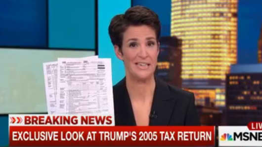 Rachel Maddow holding a copy of Donald Trump's 2005 tax return on The Rachel Maddow Show.
