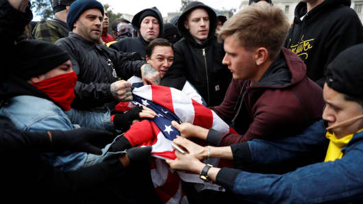 Supporters of President Donald Trump, right, and anti-Trump protesters fight for a U.S. flag.