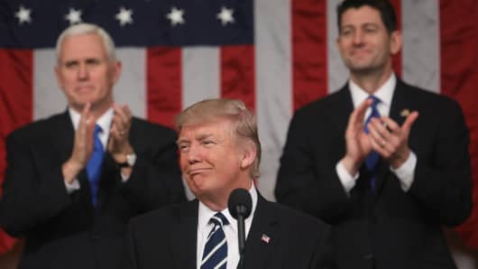 Vice President Mike Pence (L) and Speaker of the House Paul Ryan (R) applaud as US President Donald J. Trump (C) arrives to deliver his first address to a joint session of Congress from the floor of the House of Representatives in Washington, United States on February 28, 2017.