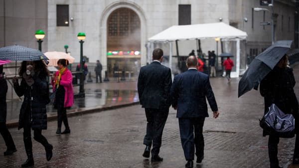 Pedestrians walk along Wall Street in front of the New York Stock Exchange.