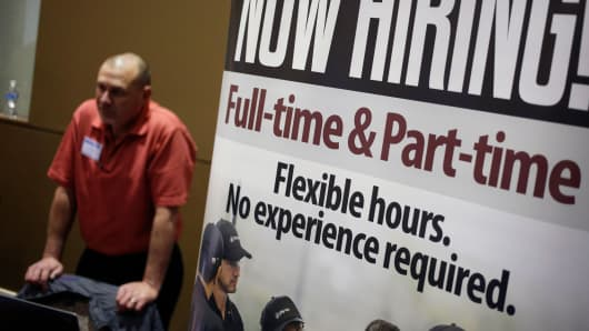 A 'Now Hiring!' sign stands on display next to the Jiffy Lube International booth during a Job News USA career fair in Overland Park, Kansas.
