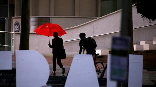 A woman holds an umbrella as a cyclist rides nearby on a rainy day in the central business district (CBD) of Sydney, Australia, March 7, 2017.