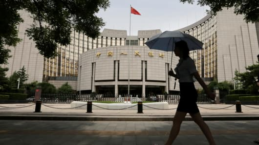 A woman walks past the headquarters of the People's Bank of China in Beijing, China.