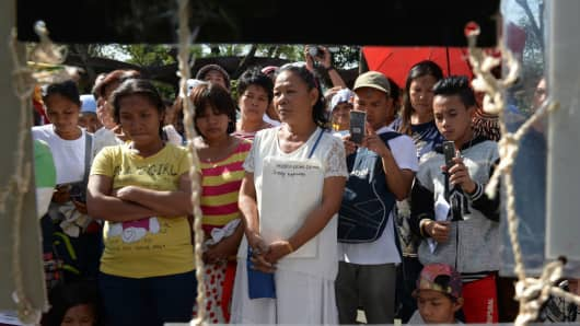 Relatives of victims of extra-judicial killings in President Rodrigo Duterte's drug war stand in front of a photo exhibit of victims during a gathering on the grounds of a church in Manila on March 1, 2017.