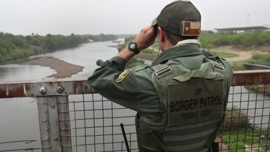 A U.S. Border Patrol agent scans the U.S.-Mexico border while on a bridge over the Rio Grande on March 13, 2017 in Roma, Texas.