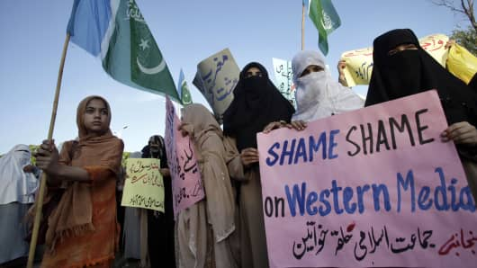 A girl holds a flag of Islamic political party Jamaat-e-Islami while taking part in a protest with others in Islamabad on May 20, 2010, against an online competition to draw pictures of Prophet Mohammad on Facebook which Muslims deem blasphemous. (File photo).