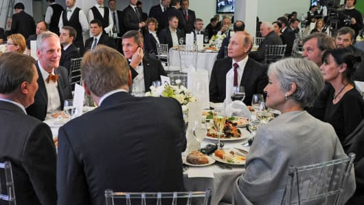 In this file photo taken on Thursday, Dec. 10, 2015, Russian President Vladimir Putin, center right, with retired U.S. Lt. Gen. Michael T. Flynn, center left, and Serbian filmmaker Emir Kusturica, obscured second right, attend an exhibition marking the 10th anniversary of RT (Russia Today) 24-hour English-language TV news channel in Moscow, Russia.