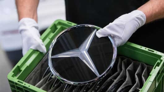 An employee holds a Mercedes-Benz badge on the assembly line at the automaker's factory in Bremen, Germany.