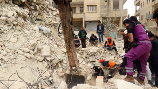 Civil Defence members and civilians remove rubble in a damaged site after an airstrike on Idlib city.