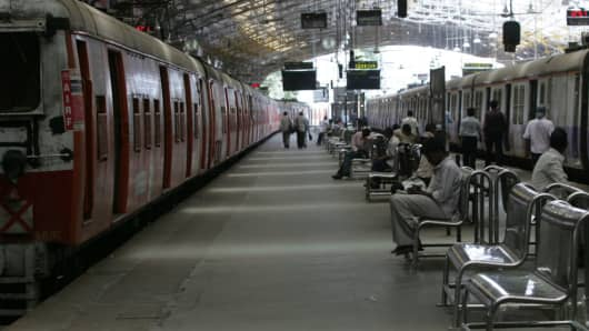 A commuter waits for a train at a train station in Mumbai.