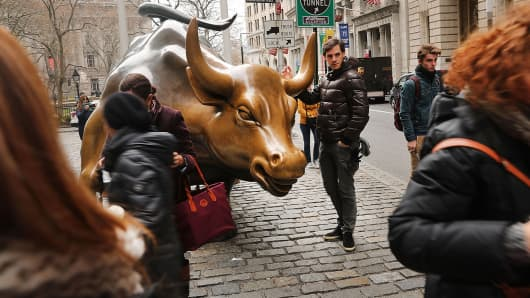 Tourists take a picture with the market bull near the New York Stock Exchange.