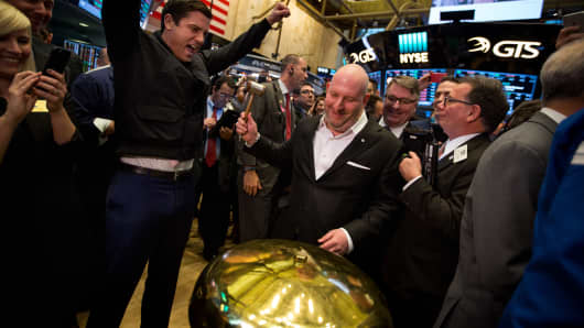 Dani Reiss, chief executive officer and president of Canada Goose Holdings Inc., center, rings a ceremonial bell as Tom Farley, president of the NYSE Group, left, cheers on the floor of the New York Stock Exchange (NYSE) during the company's initial public offering (IPO) in New York.