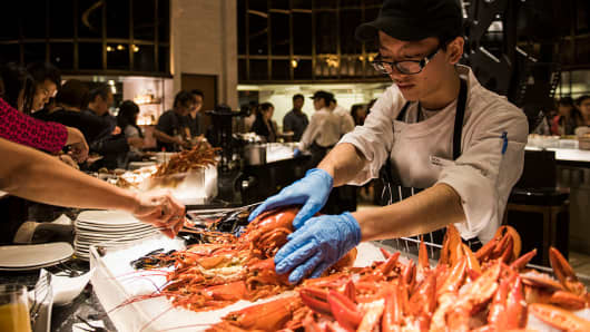 An employee arranges lobsters at a buffet in the Studio City casino resort in Macau, China.