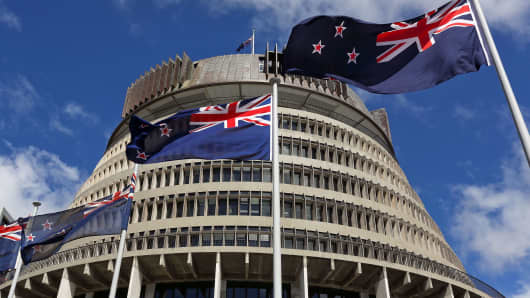 New Zealand flags fly in front of The Beehive during the Commission Opening of Parliament at Parliament in Wellington, New Zealand.
