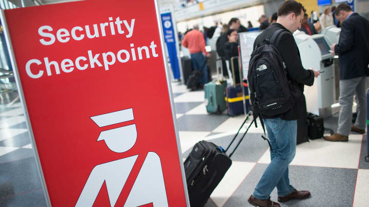 A sign directs travelers to a security checkpoint staffed by Transportation Security Administration (TSA) workers at O'Hare Airport.