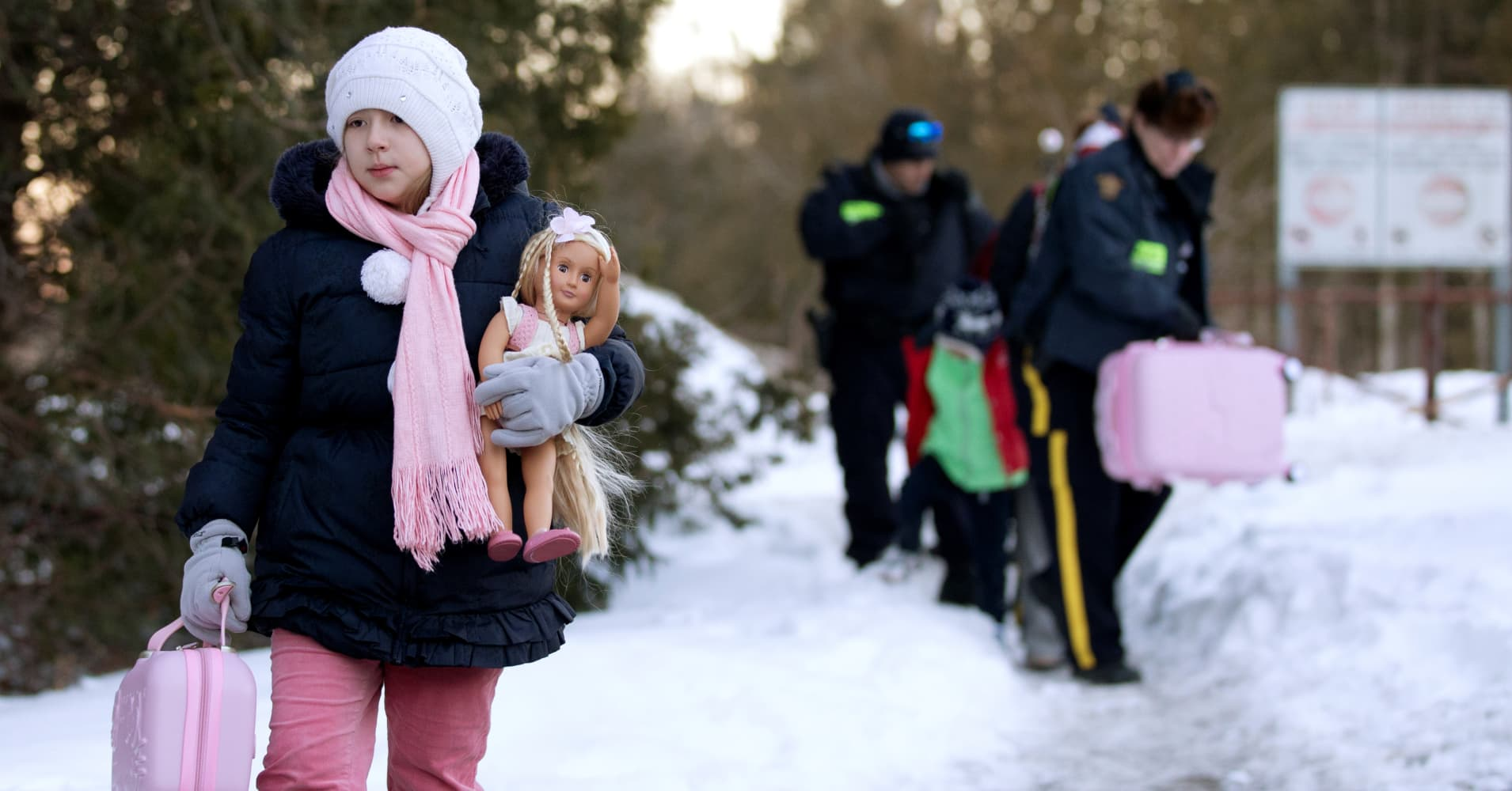 A young girl carries her doll and suitcase as her family that claimed to be from Turkey are met by Royal Canadian Mounted Police (RCMP) officers after they crossed the U.S.-Canada border illegally leading into Hemmingford, Quebec, Canada, March 20, 2017.