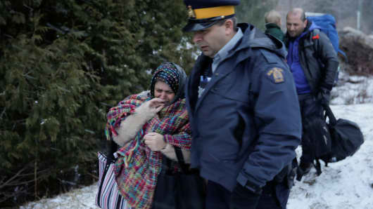 A woman that claimed to be from Syria cries as she is detained by a Royal Canadian Mounted Police (RCMP) officer after crossing the U.S.-Canada border into Hemmingford, Quebec.