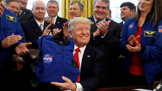 President Donald Trump receives a NASA jacket during a signing ceremony for S442, the NASA transition authorization act, in the Oval Office of the White House in Washington, March 21, 2017.