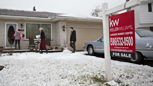 Prospective home buyers and a real estate agent, center, enter a home for sale in Warren, Michigan.