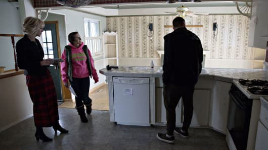 A real estate agent, left, shows prospective buyers the kitchen area inside a home for a possible sale in Warren, Michigan.