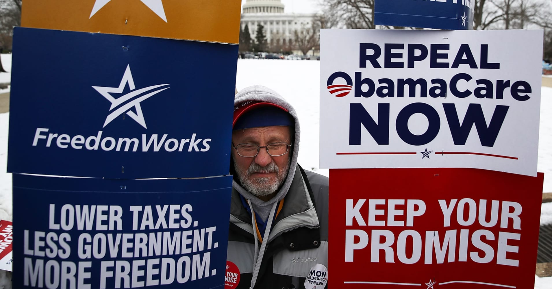 A protester holds signs during a Freedom Works rally against the proposed GOP health care plan at Upper Senate Park across from the U.S. Capitol on March 15, 2017 in Washington, DC.