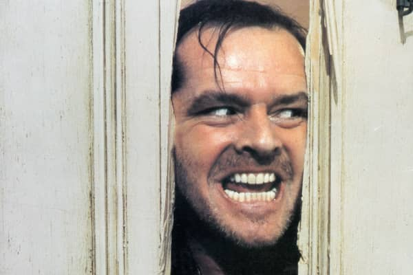 Jack Nicholson peering through axed in door in lobby card for the film 'The Shining', 1980.
