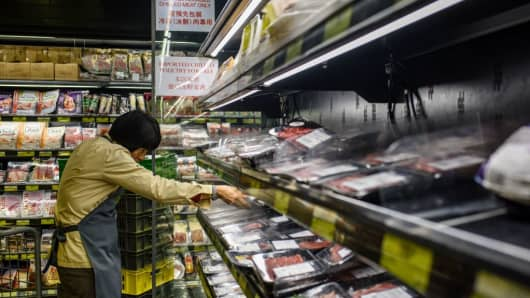 A member of staff clears packs of imported meat from Brazil off the shelves of a supermarket in Hong Kong on March 21, 2017.