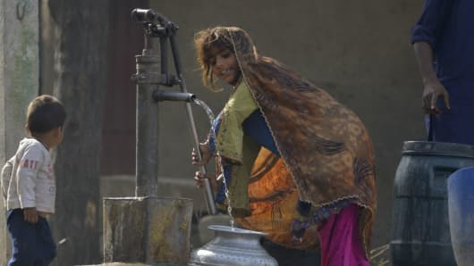 A Pakistani girl fills a pot with water from a hand pump on the outskirts of Lahore on March 21, 2017, ahead of World Water Day.