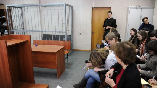 Journalists sit next to the empty defendant's cage in the Tverskoy district court of Moscow on March 27, 2013, during a hearing in the posthumous trial of lawyer Sergei Magnitsky for tax evasion, days after Russia closed a probe into the circumstances of his prison