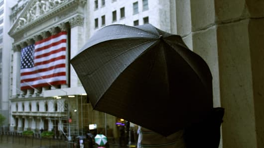 A pedestrian stands on the steps of Federal Hall in the rain outside the the New York Stock Exchange (NYSE).