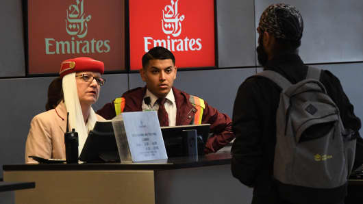 A passenger buys a ticket at a Emirates Airline counter in Los Angeles International Airport.