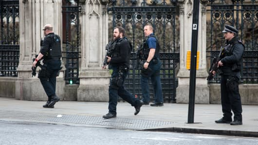 Armed officers attend to the scene outside the Houses of Parliament on March 22, 2017 in London, England.